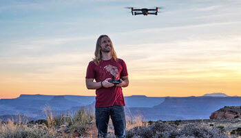 Man operating a drone while stanging on a cliff in Grand Canyon