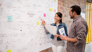 Two people looking at the board, figuring out the key elements of a winning business plan for their business