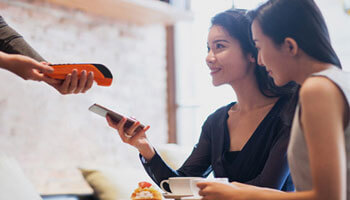 Two women paying with a smartphone at a restauraunt