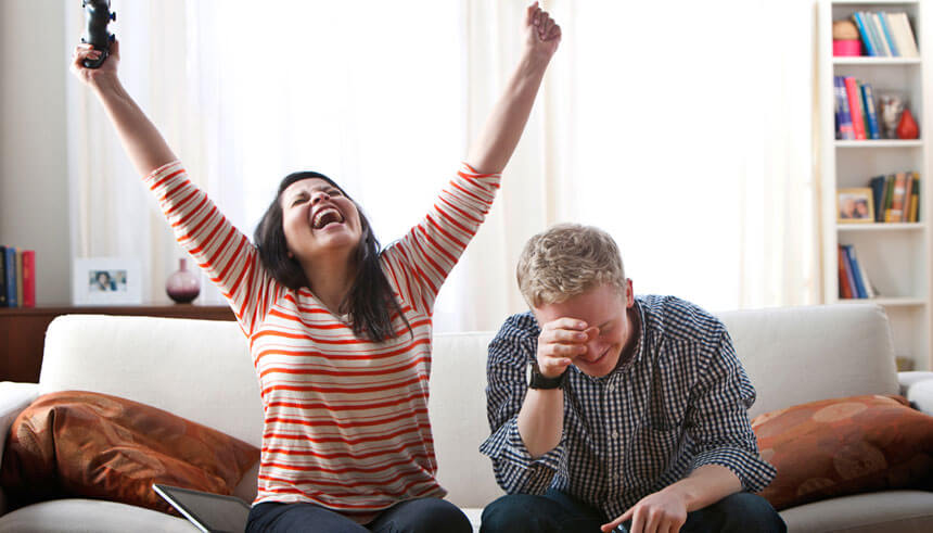 Cheering woman defeating boyfriend at video games on sofa