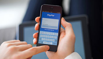 A person accessing PayPal on their phone