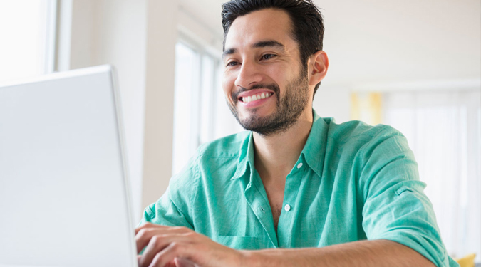 Smiling male looking at a laptop for online banking