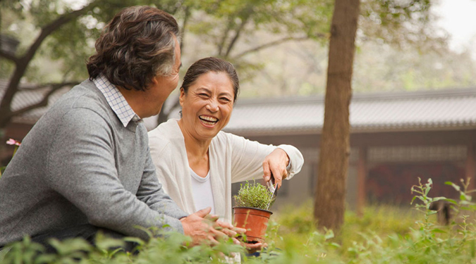 Happy retired couple laughing and planting in their garden