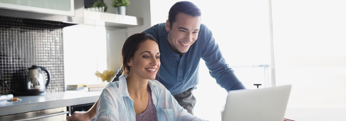 Smiling couple looking at laptop for checking account options