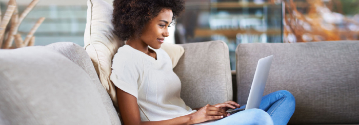 Smiling female using laptop at home to send cash online