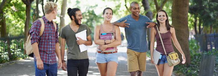 Ethnically diverse group of smiling students walking on college campus