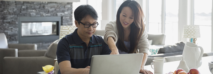 Smiling couple looking at laptop for savings account