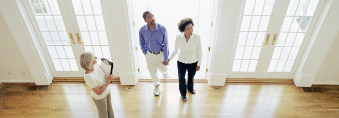 Couple holding hands and entering home with home mortgage loan agent