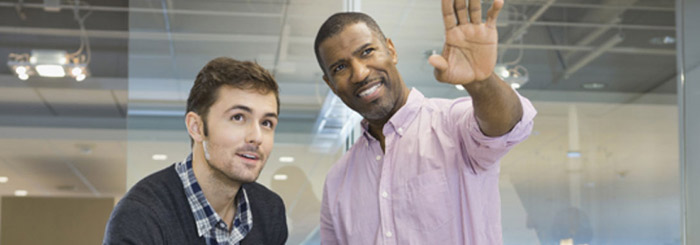 Small business owner and employee looking up optimistically