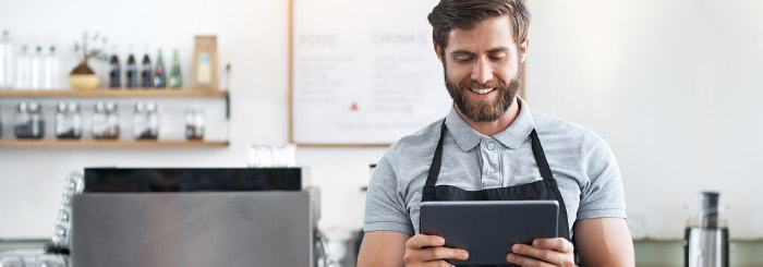 Small business owner on his tablet for online banking and account balance