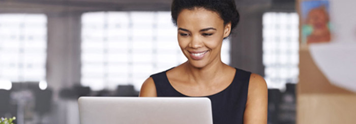 Smiling female on her laptop for electronic deposit secure safe