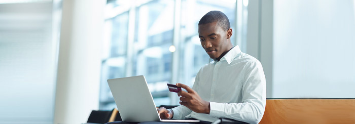 Business man with laptop looking at his business credit card to make online payment