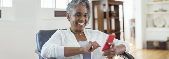 Smiling female looking at her phone for mobile banking