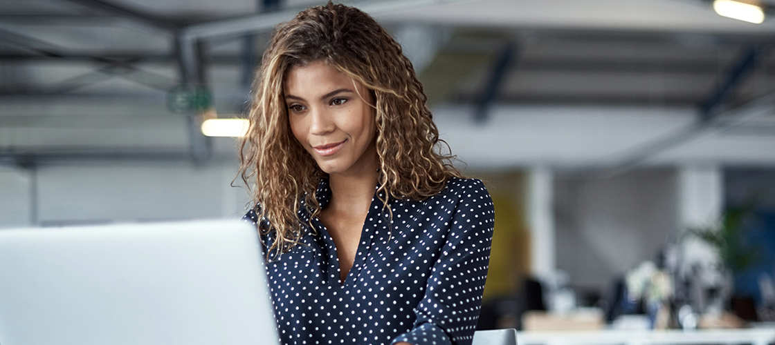 Optimistic female sitting in front of her computer at work