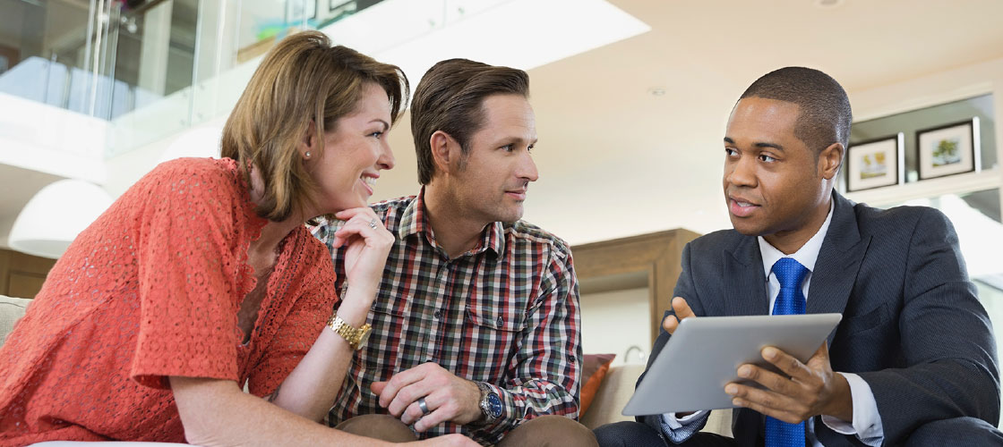 Couple receiving advice from investment planning consultant holding a tablet