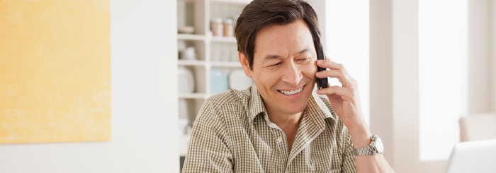 Smiling optimistic man on the phone with a loan servicing specialist