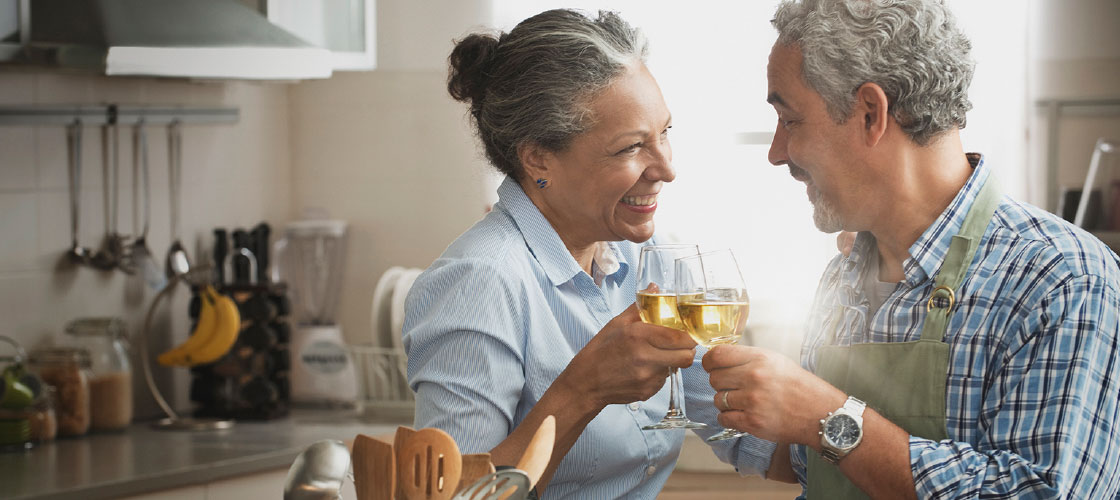 Happy retired senior couple toasting wine glasses in their kitchen