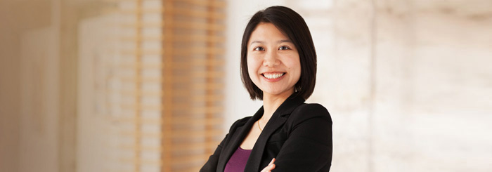 Smiling female bank employee folding arms