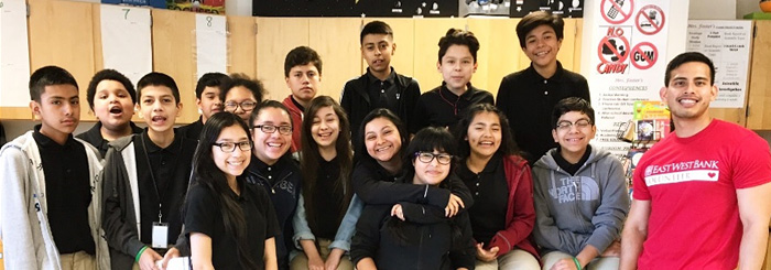 Bank employee poses with class of smiling students