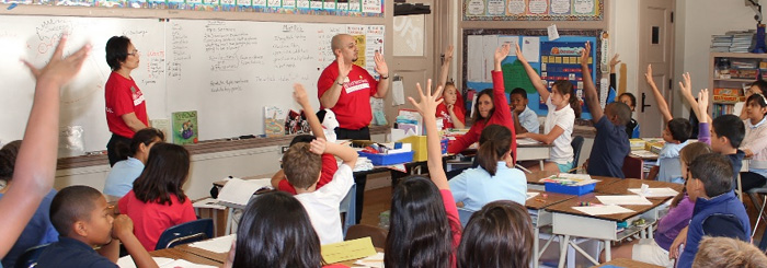 Bank volunteers teach financial literacy to a classroom of young students