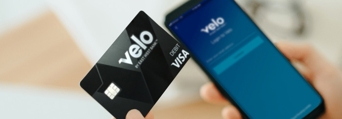 Woman holding a Velo debit card and mobile phone logging into the Velo mobile app